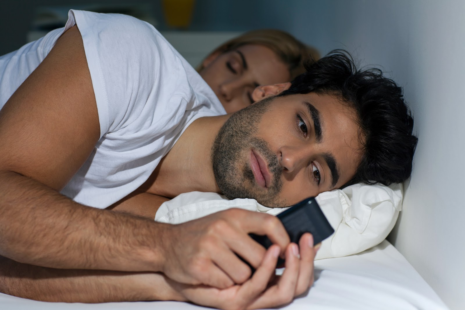guy-checking-cell-in-bed