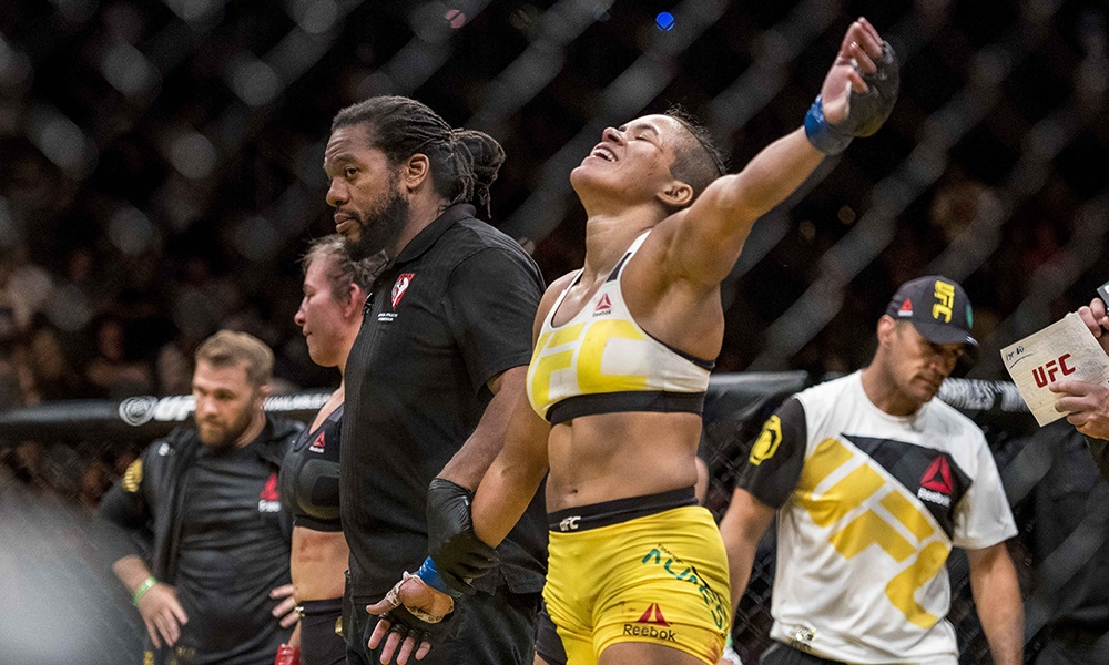 Jul 9, 2016; Las Vegas, NV, USA;  Amanda Nunes (blue gloves) reacts after defeating Miesha Tate (red gloves) during UFC 200 at T-Mobile Arena. Nunez won by rear naked choke. Mandatory Credit: Joshua Dahl-USA TODAY Sports