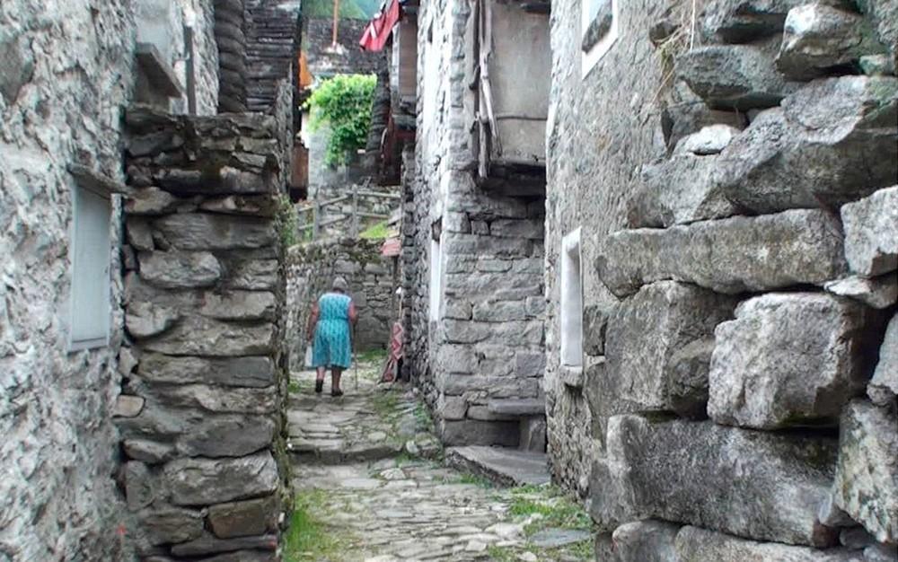 2 senhora caminha por uma rua estreita de corippo ladeada por construcoes de pedra