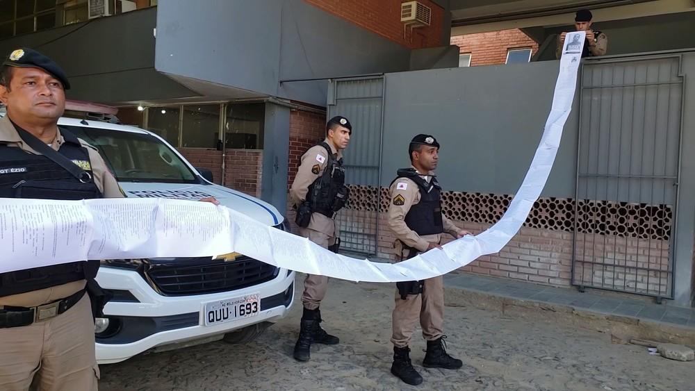 policiais seguram ficha criminal de suspeito